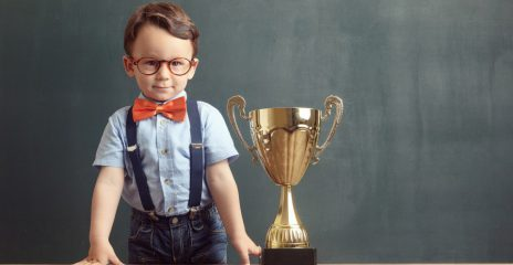 A child in a bowtie next to a trophy, the trophy reaches his shoulders.