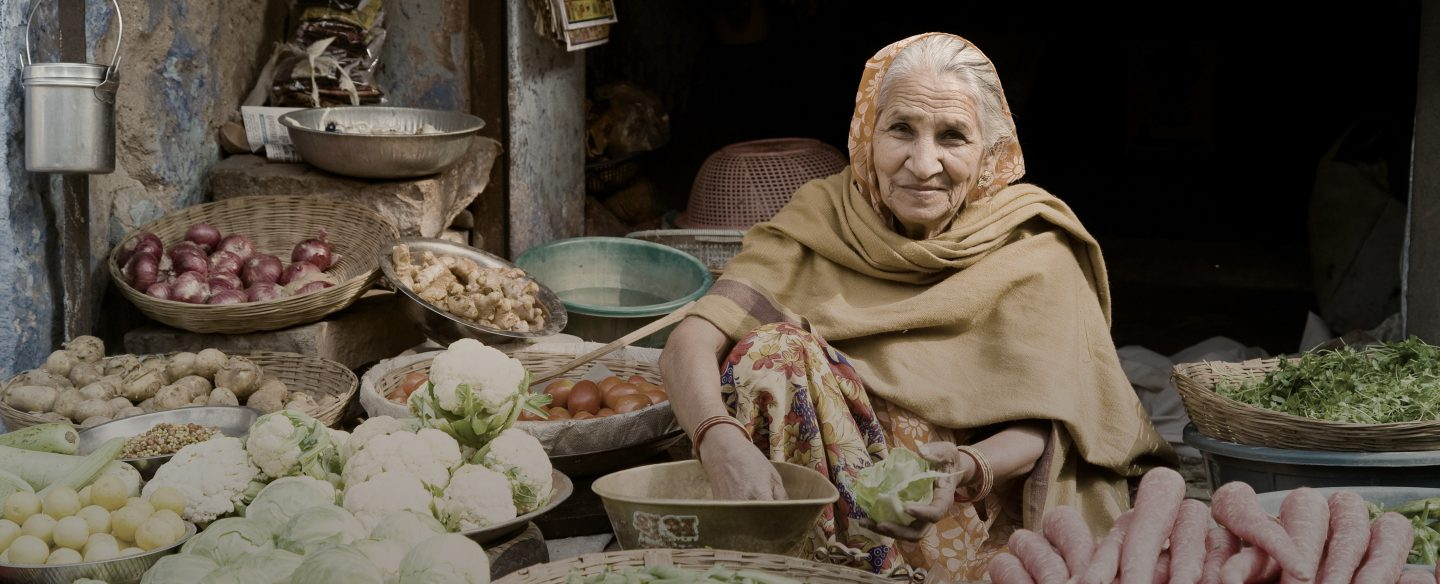 An elderly woman sitting at her shop in a market surrounded by baskets of fresh vegetables.