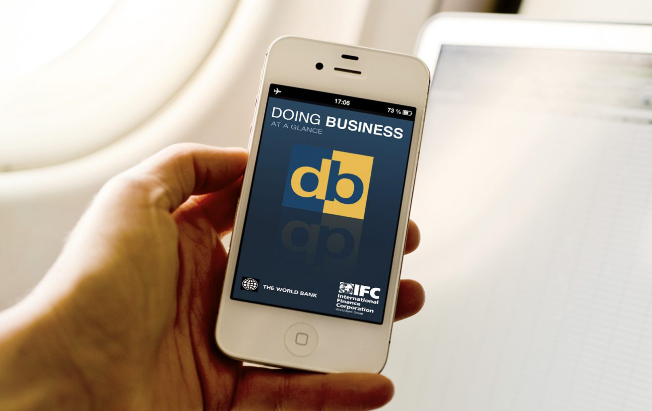 A man holds his phone displaying the Doing Business at a Glance app.