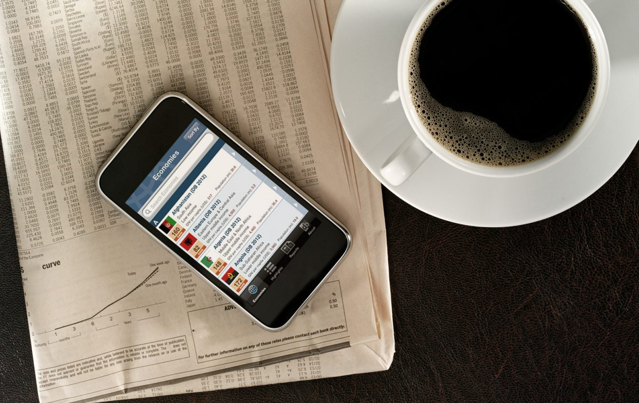 A phone sitting on newspaper next to a cup of coffee, the phone shows the Doing Business at a Glance app.