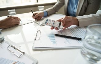 Professionals sitting around a desk with various charts. A woman holds the Doing Business at a Glance app while people take notes.