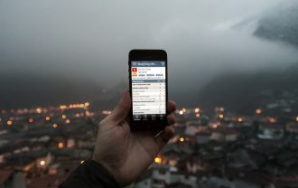 A man holds the Doing Business at a Glance app in front of a backdrop of a foggy city.